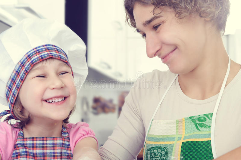 Cute girl with her mother bake cookies at home. Cute little girl with her mother bake cookies at home kitchen royalty free stock images