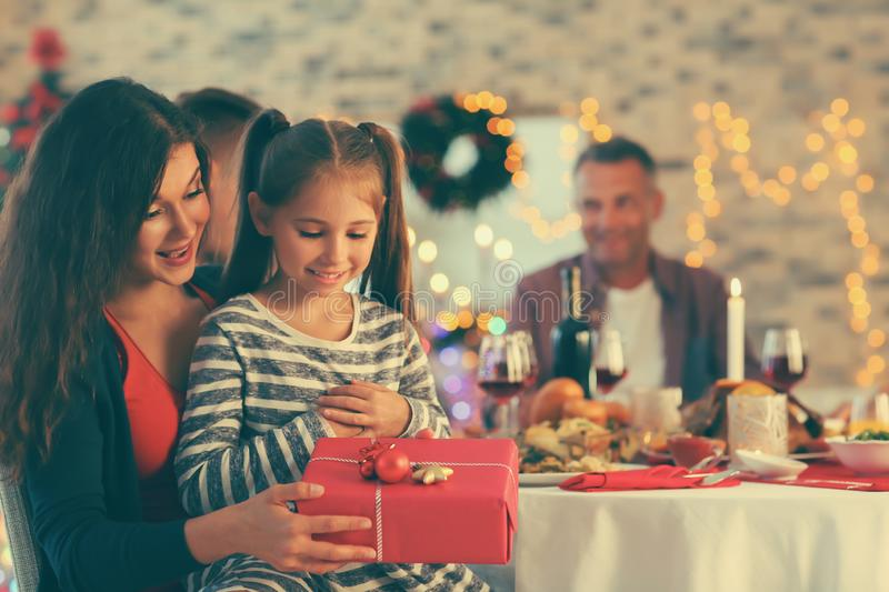 Cute girl and her mother with Christmas gift at home stock photo