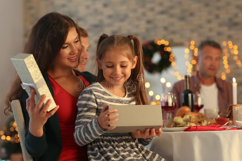 Cute girl and her mother opening Christmas gift at home royalty free stock photo