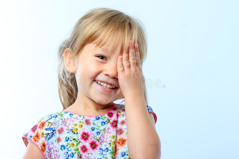 Cute girl hiding eye with hand. royalty free stock image