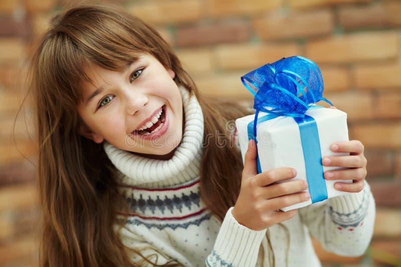 Cute girl holding a gift stock photos