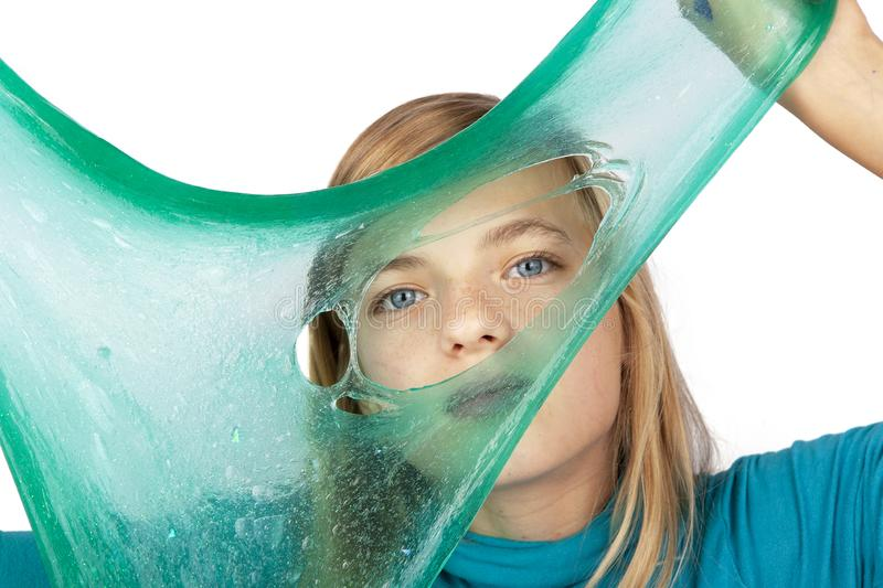 Cute girl holding a green slime with a hole in front of her face royalty free stock image