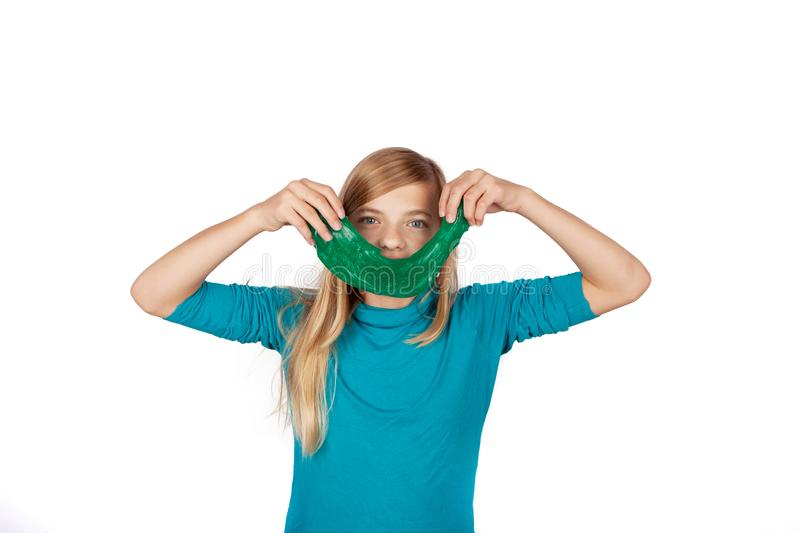 Cute girl holding a green slime toy and making smile with it royalty free stock images