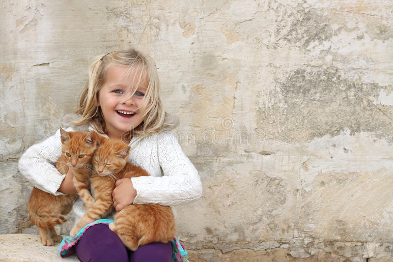 Cute girl holding kittens royalty free stock photography