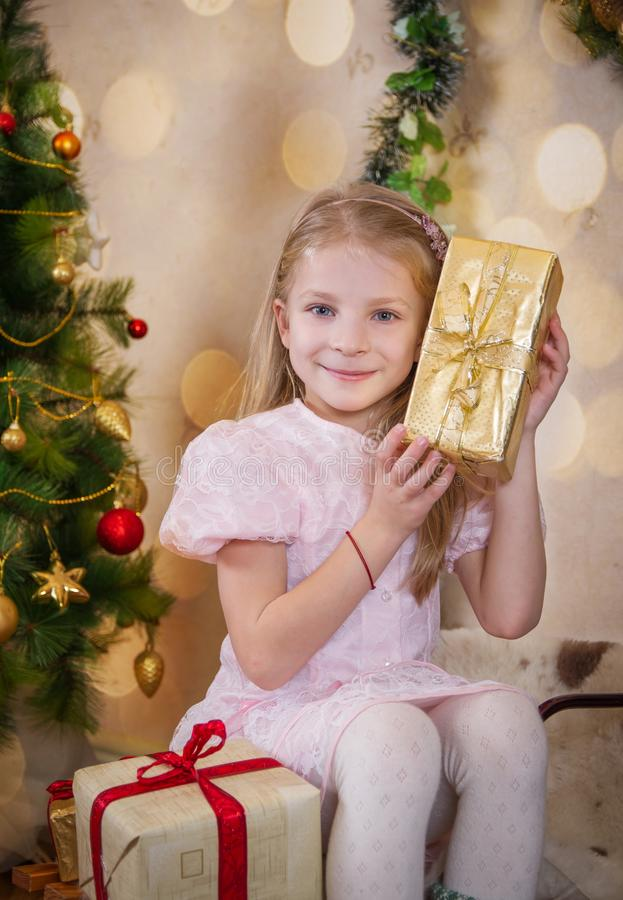 Cute girl holding present and wondering at Christmas stock photography