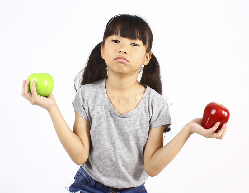 Cute girl holding red and green apple royalty free stock photos