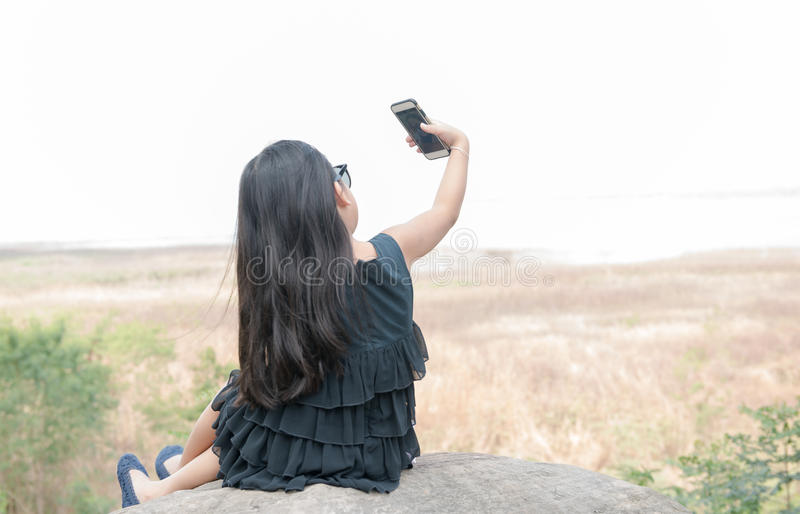 Cute girl holding smartphone to taking selfie. stock photography