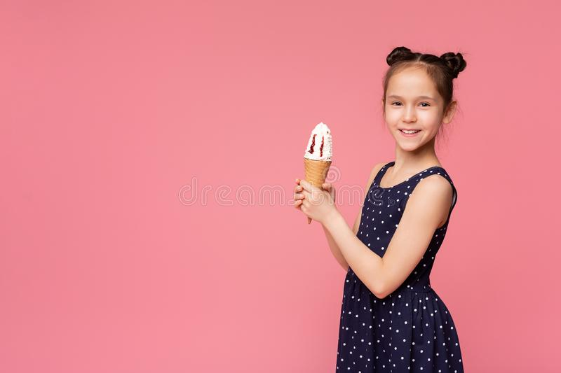 Cute girl holding two ice cream cone and smiling on camera. Enjoy sweet summer time. Cute girl holding two ice cream cone and smiling on camera, pink studio stock image