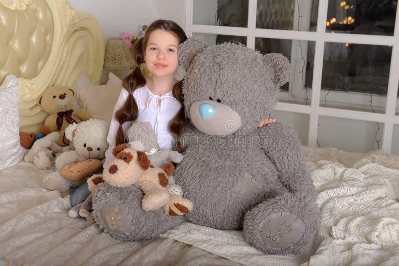 Cute girl hug big bear on bed royalty free stock photo
