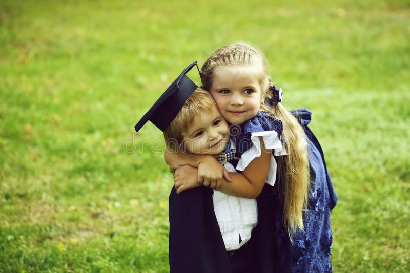 Cute girl hugging happy boy in graduation hat and robe. Cute little girl with long hair in blue dress hugging happy small boy in black graduation hat or cap and royalty free stock photography