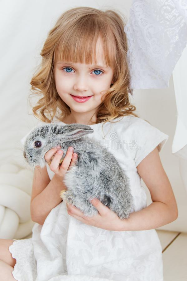 Cute girl hugging with rabbit while sitting on the floor at home stock photos