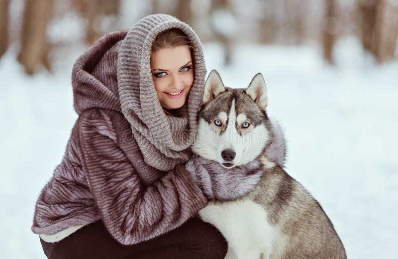 Cute girl with a husky dog in the winter forest background, close up stock photography