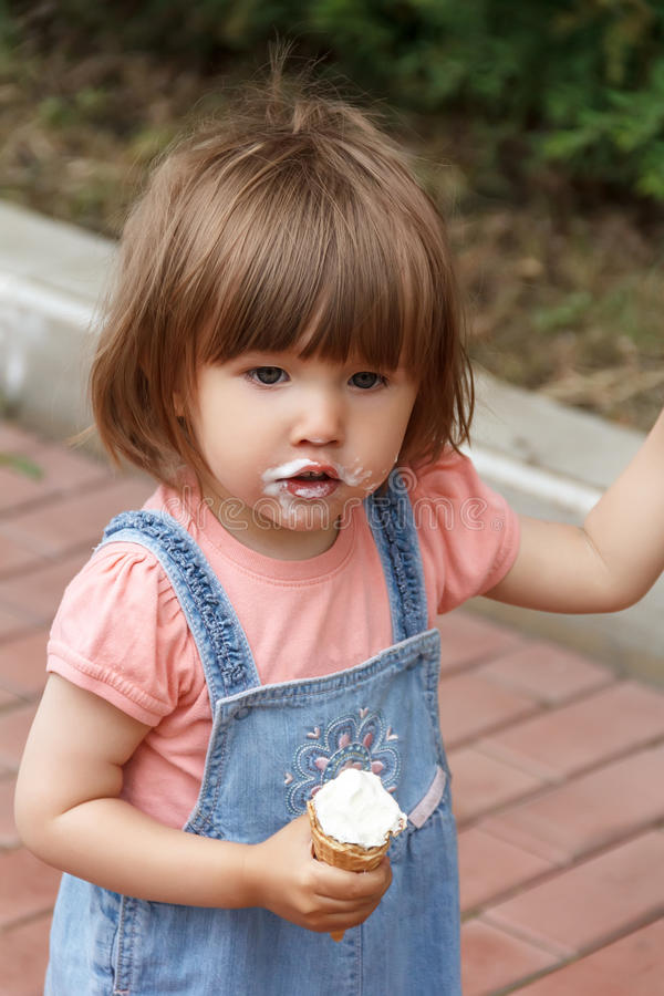 Cute girl with icecream in hand. Photo of cute girl are eating icecream in summer royalty free stock image