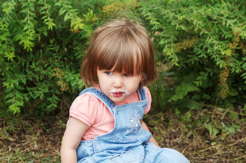 Cute girl with icecream mouth in summer. Photo of cute girl with icecream mouth in summer royalty free stock image