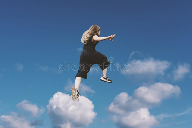 Cute girl jumping funny in clouds stock photo