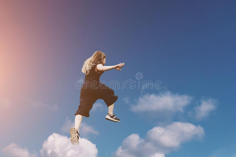 Cute girl jumping funny in clouds stock image