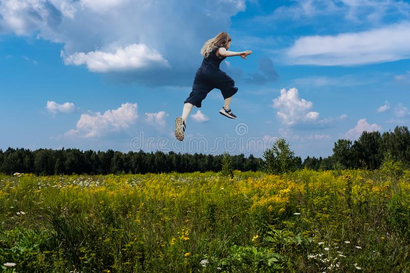Cute girl jumping funny in clouds stock photography
