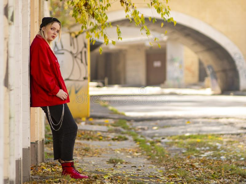 Cute girl in a knitted hat red jacket and red boots standing near a wall in full growth in the outdoor stock photo