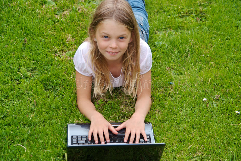 Cute girl with laptop, looking at camera stock photography