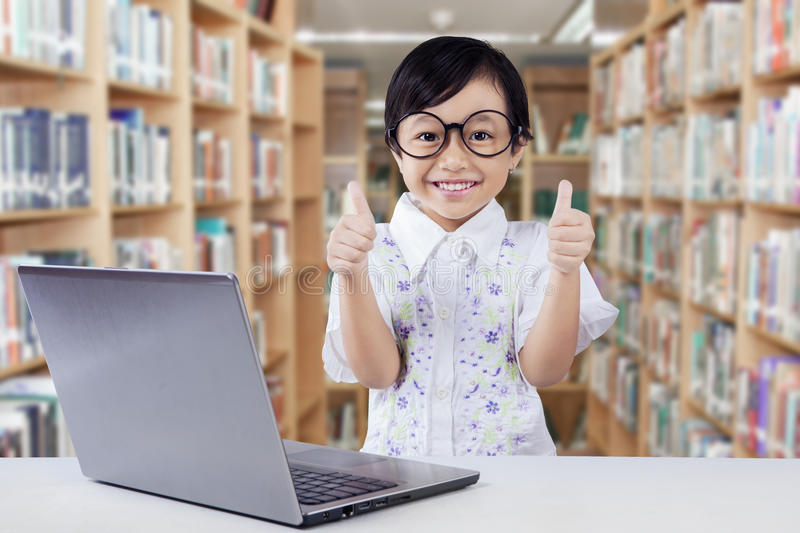 Cute girl with laptop shows thumbs up. Portrait of adorable little girl with laptop computer showing thumbs up on the camera in the library royalty free stock image