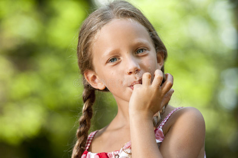 Cute girl licking off chocolate fingers.