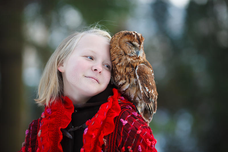 Cute girl with little owl. Cute girl in red scarf standing with little owl in a park