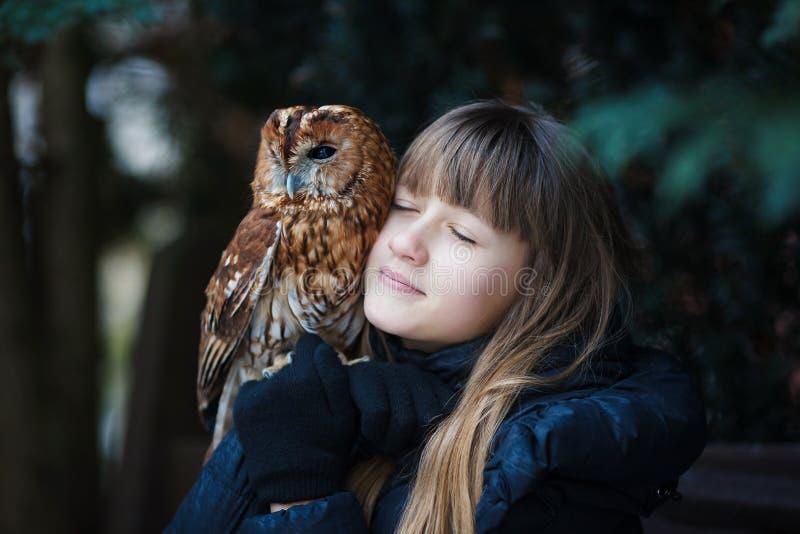 Cute girl with little owl stock photos