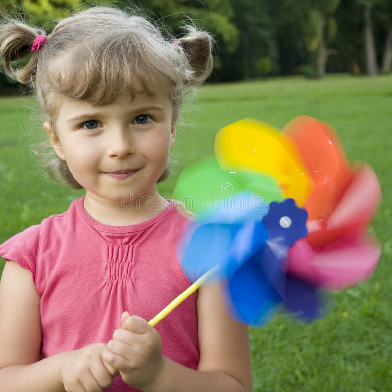 Cute girl with little windmill stock photos