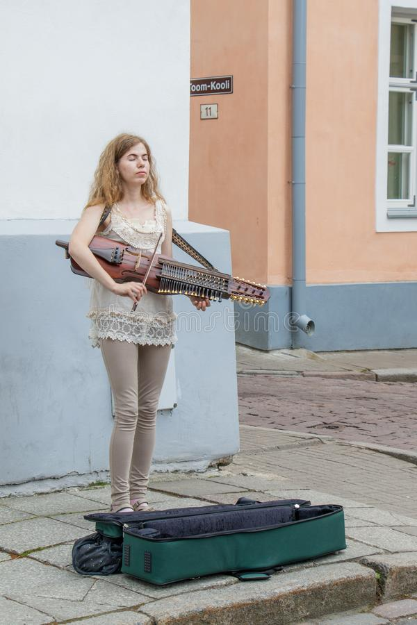 A cute girl with long blonde hair plays for tourists on a large stringed musical instrument on the street of the Old Town royalty free stock photos