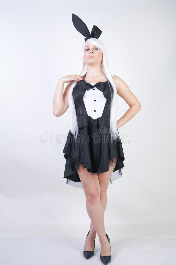 Cute girl with long white hair with Bunny ears in rabbit costume on white background in Studio. a woman with a plus size body stan stock photo