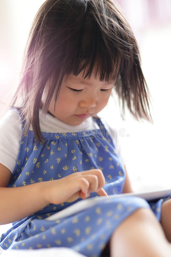 Cute girl is looking tablet. Pc in livingroom, asian stock image
