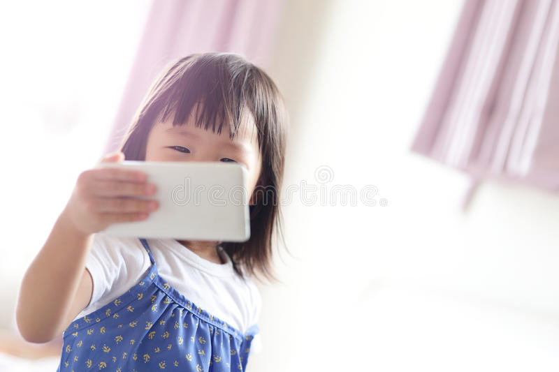Cute girl is looking tablet. Pc in livingroom, asian royalty free stock photography