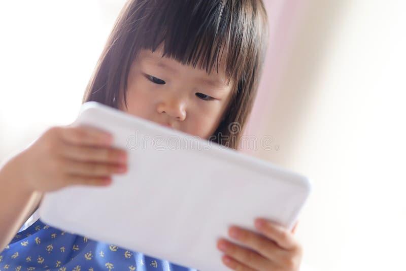 Cute girl is looking tablet. Pc in livingroom, asian stock photos