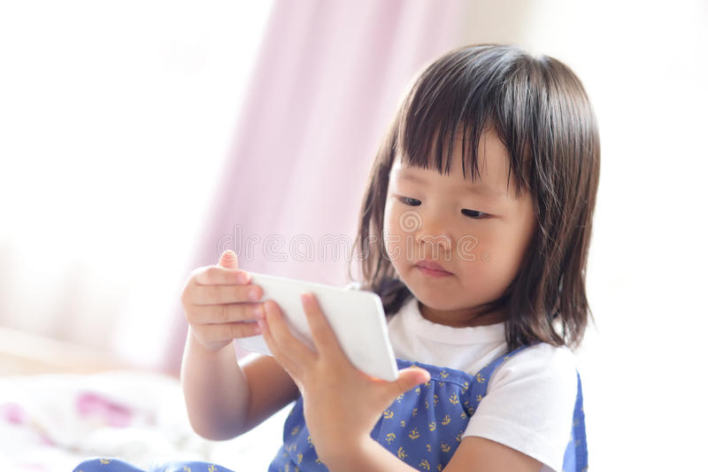 Cute girl is looking tablet. Pc in livingroom, asian stock photo