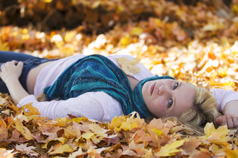 Cute girl lying in the fall leaves royalty free stock image