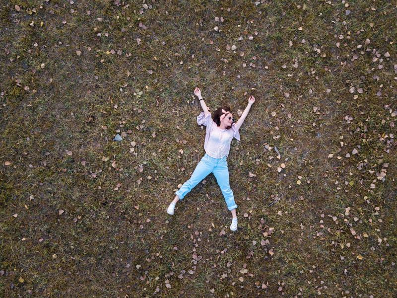 Cute girl lying in the grass aerial stock image