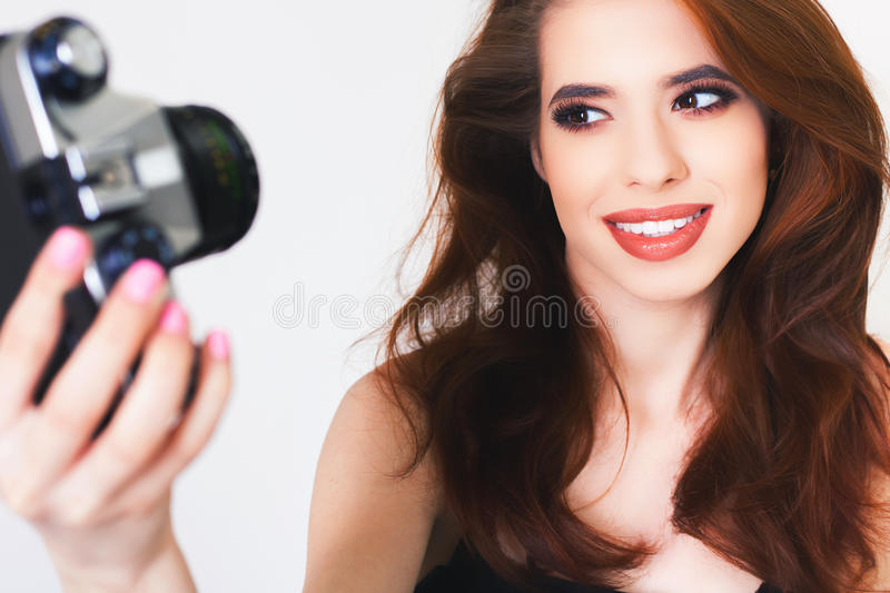 Cute girl make a foto selfie at vintage camera. Image of cute girl make a photo selfi at vintage camera. Take a photograph of herself. Funny, party. Beauty royalty free stock images