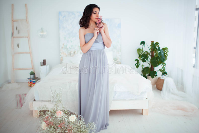 Cute girl with makeup in a blue evening dress standing beside the bed. Beautiful cozy interior in the background royalty free stock photography