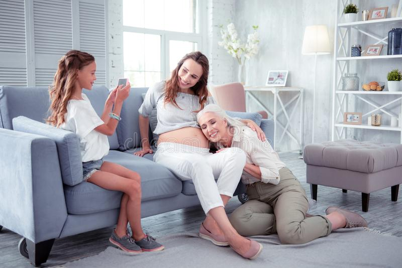 Cute girl making photo of her pregnant mom and grandmother stock photo