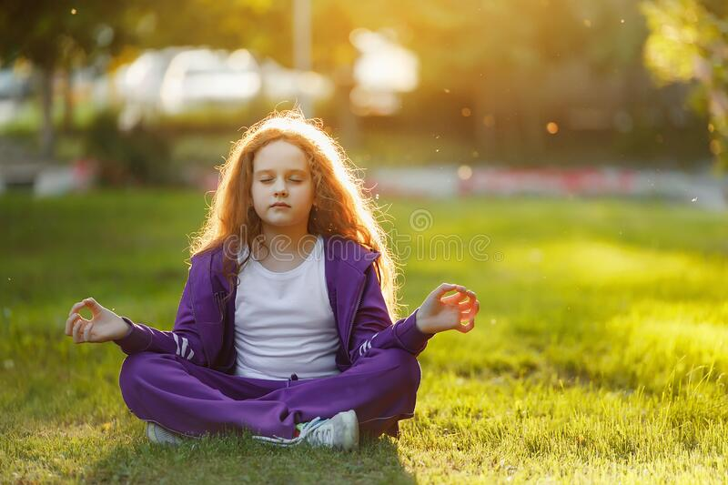 Cute girl meditation in summer park stock photography