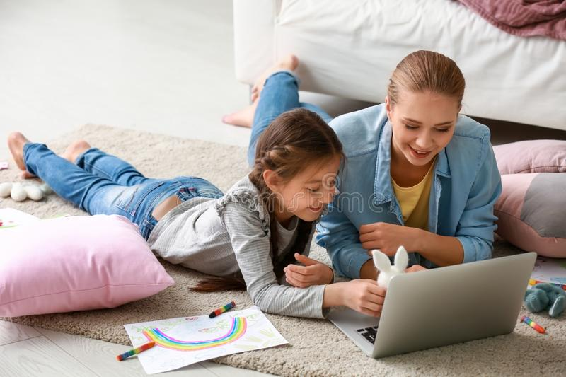 Cute girl with mother doing homework at home stock photography