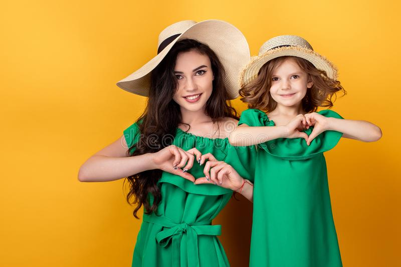 Cute girl and mother holding hands in heart shape on white background stock photos