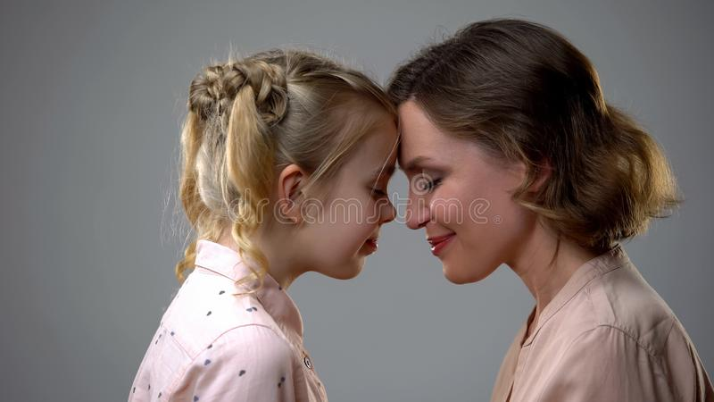 Cute girl and mother touching foreheads, female friendship, family support stock images