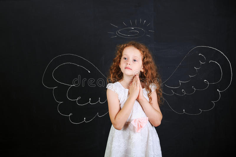 Cute girl near angel wings drawn on a blackboard. Cute girl in white dress folded her hand with praying, stand near angel wings drawn on a blackboard royalty free stock photography