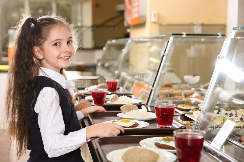 Cute girl near serving line with healthy food in canteen stock photo
