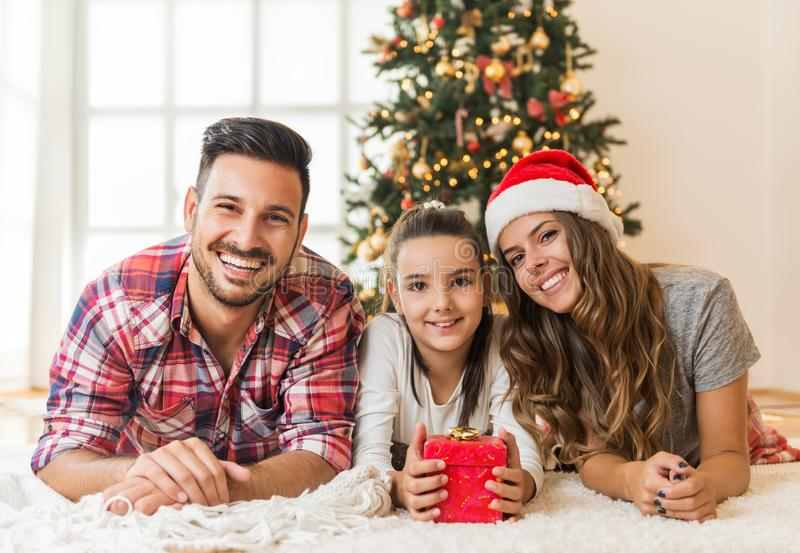 Cute girl opening a magical present on a Christmas morning with her family. At home royalty free stock photo