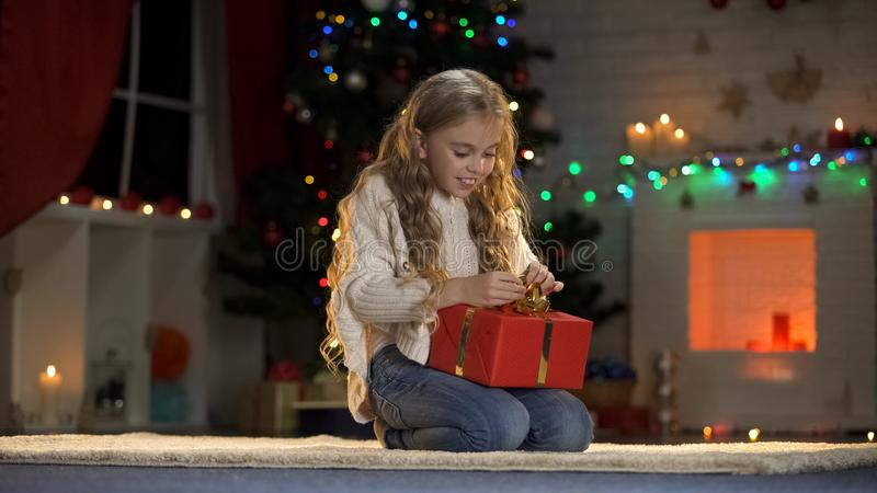 Cute girl opening present under Christmas tree, gift from Santa, magic eve stock photos
