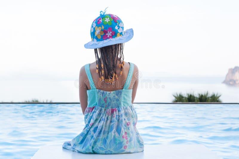 Cute girl overlooking ocean from infinity pool. stock image
