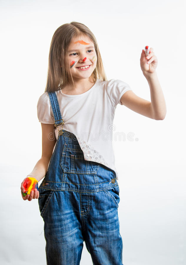 Cute girl in paint drawing with paint tube in the air. Portrait of cute girl in paint drawing with paint tube in the air stock photo