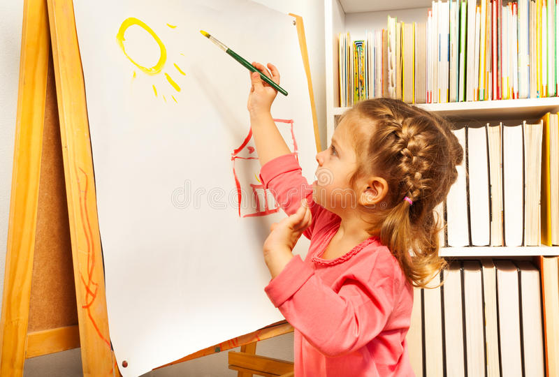 Cute girl painting brush watercolors on a easel royalty free stock photography